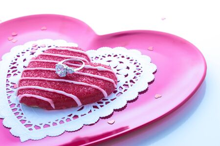 Sugar cookie with engagement ring on pink plate with white doily photo