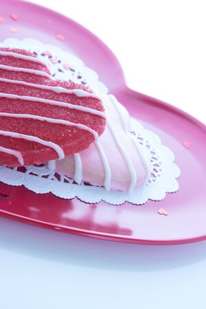Sugar cookie icing on pink plate with white doily and little shiny red hearts Stock fotó