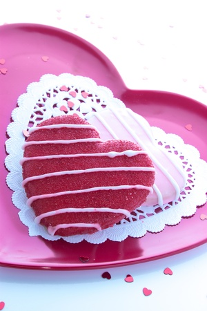 Sugar cookie icing on pink plate with white doily and little shiny red hearts photo