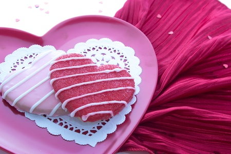 Sugar cookie on pink plate with white doily and red napkin photo
