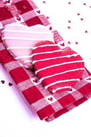 Sugar cookies with icing on red plaid napkin and shiny red hearts Stock Photo