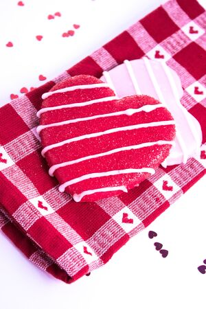 Sugar cookies with icing on red plaid napkin and shiny red hearts photo