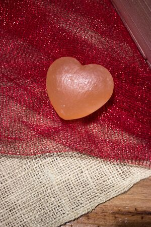 Pink Himalayan sea salt heart on red sparkly fabric and white burlap Stock Photo - 17709713