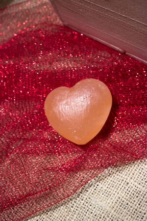 Pink Himalayan sea salt heart on red sparkly fabric and white burlap Stock Photo - 17709710