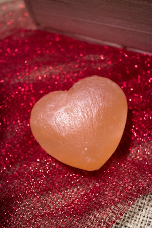 Pink Himalayan sea salt heart on red sparkly fabric and white burlap Stock Photo - 17709701