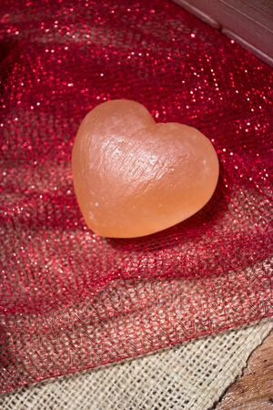 Pink Himalayan sea salt heart on red sparkly fabric and white burlap photo