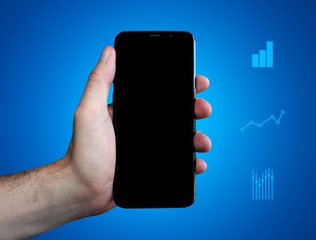 Hand holds phone (cell phone) and show display. Charts on blue background. Business