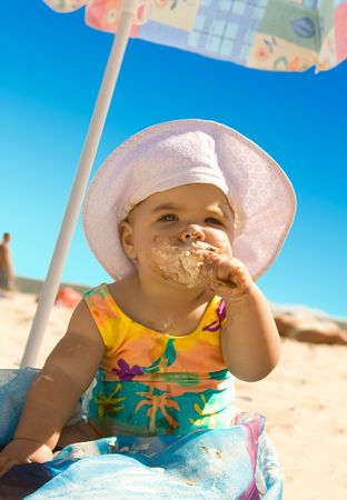 The little girl on the beach under an umbrella with ice cream photo