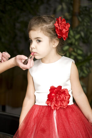 Little girl doing makeup before dance competitions photo