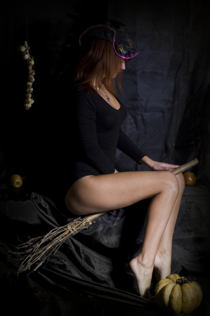 young sexy sitting on a hat and a witch on a broom on a black background photo