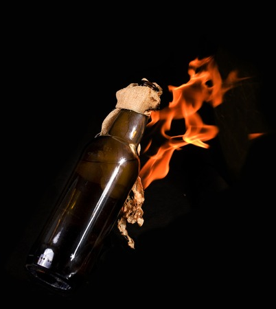 Thrown bottle with Molotov cocktail and burning on black background photo