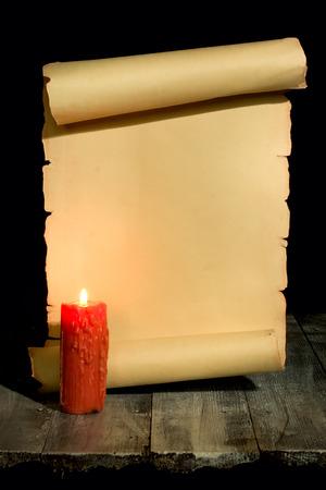 schriftrolle: Alte Rolle gerollt in Holzuntergrund mit Kerze