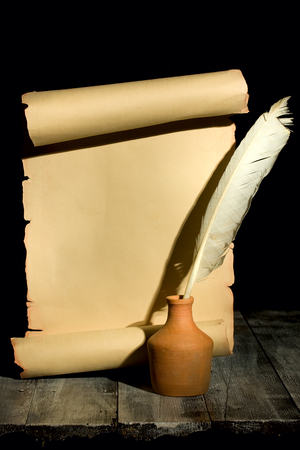 pen and paper: Ancient scroll rolled in wooden Background with Guill Pen