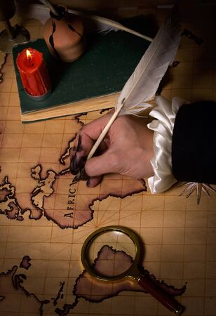 cartography: Hand with ink stained fingers draws map of the world ancient quill pen