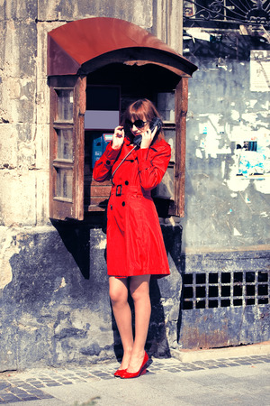 pay phone: girl in a bright coat of calls to the pay phone on the street of Lviv Stock Photo