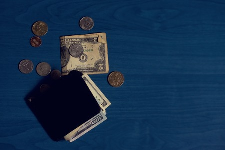 notecase: Clip for money with dollar banknotes and some coins scattered around on blue background Stock Photo