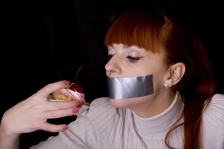 taped: The girl, whose mouth sealed with tape sad looking at cake Stock Photo