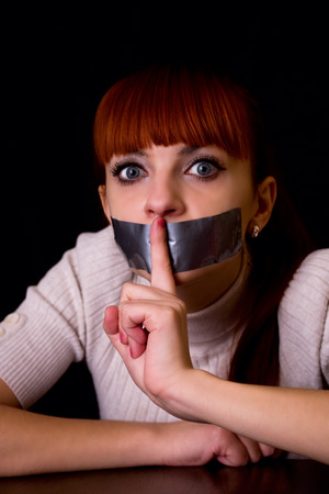 mouth: girl with her mouth sealed with tape brought finger to his mouth calling silent