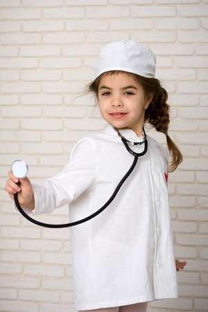 Little girl doctor in the white uniform with a stethoscope
