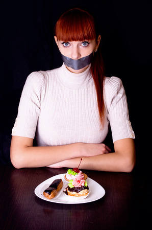 shut: The girl, whose mouth sealed with tape sad looking at plate with cakes