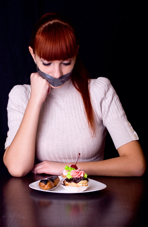 whose: The girl, whose mouth sealed with tape sad looking at plate with cakes
