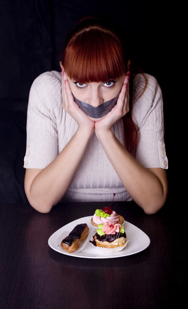 taped: The girl, whose mouth sealed with tape sad looking at plate with cakes