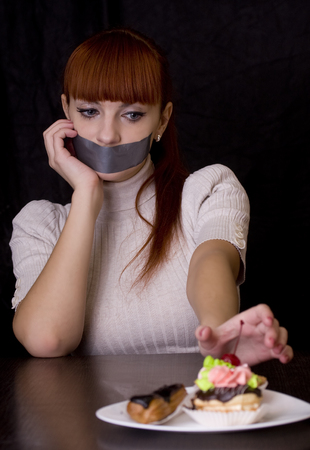 taped: The girl, whose mouth sealed with tape extends at plate with cakes