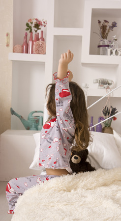 wake: The little girl woke up in a comfortable bedroom and stretches on the bed