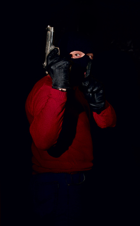 sneaks: gangster with a pistol in mask on the face sneaks into the dark