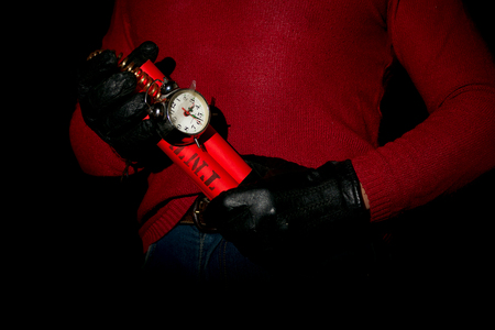 detonating: Terrorist in red sweater and gloves holds in hands time bomb