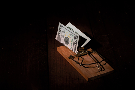 cocked: cocked mousetrap with dollar bill to attract gullible and greedy