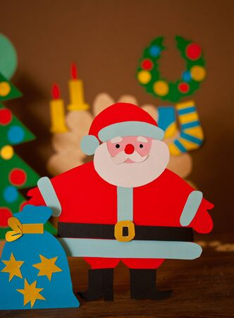 holiday gifts: funny paper Santa Claus with bag of gifts in bright holiday clothes