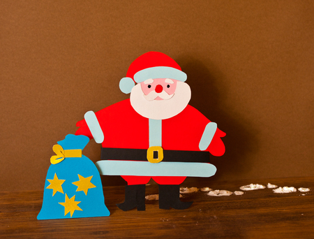 festive background: funny paper Santa Claus with bag of gifts in bright holiday clothes