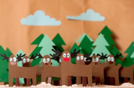 Team Reindeer Santa Claus standing in snowy forest. In front of red nosed Rudolph. The whole picture is cutting out from colored paper