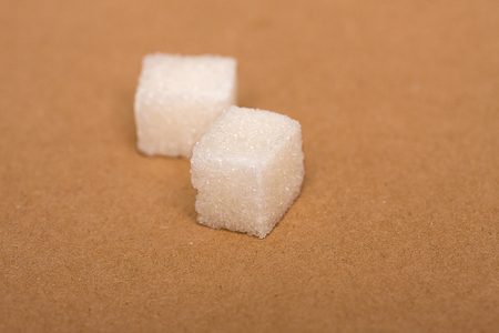 two cubes of white sugar refined on a beige background of kraft paper