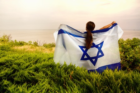 a little girl with an Israeli flag raised in her hands and behind her stands on the shore of a pond in a thicket of grass.