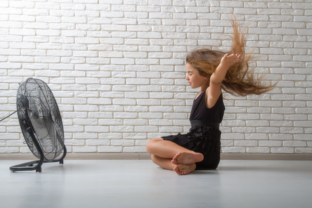 little girl struggling with heat and sitting in front of a fan with flying hair in an apartment on a bricky light wall background Reklamní fotografie