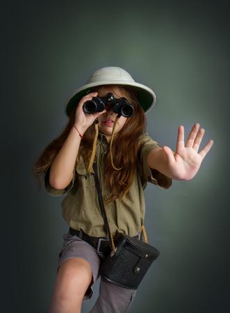 little girl in tropical uniform and cork helmet looks through binoculars