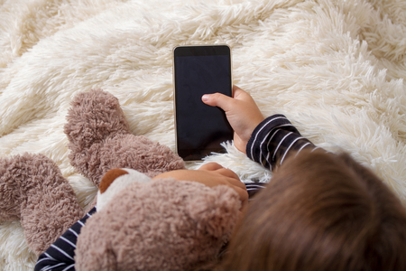 Little girl lying on the bed with her favorite teddy bear and playing a smartphone