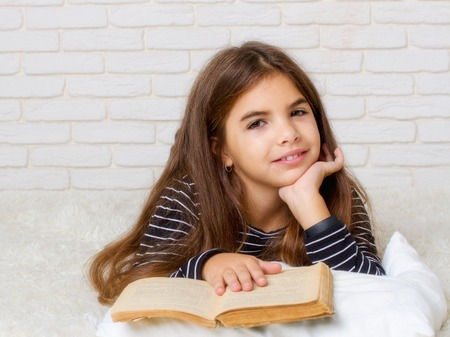 A little girl is lying on the bed holding a large old book in front of her and reading Stock Photo