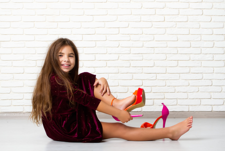 Little girl sitting on the floor trying on big bright fashionable mother's high-heeled shoes Stock fotó