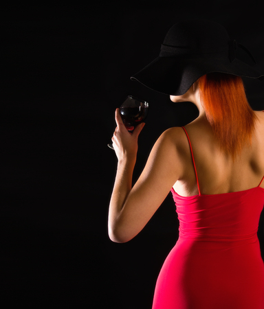 sensual girl in a bright red dress and black wide-brimmed hat stands with a glass of wine on a dark background Foto de archivo