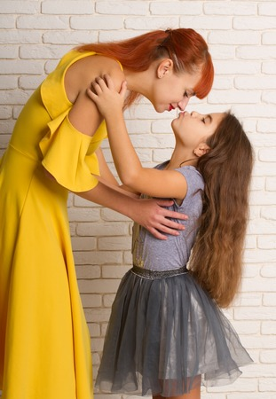 Little girl gently hugs and stretches to kiss her mom