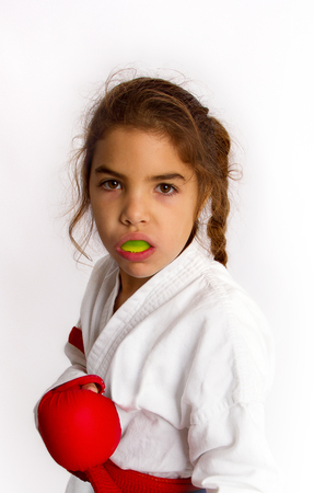 A little girl karateka in white kimono and in a red belt with a mouth guard in her lips should be ready for the fight