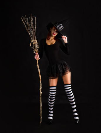sexy girl dressed as a medieval witch stands with a broom in her hands Stock Photo