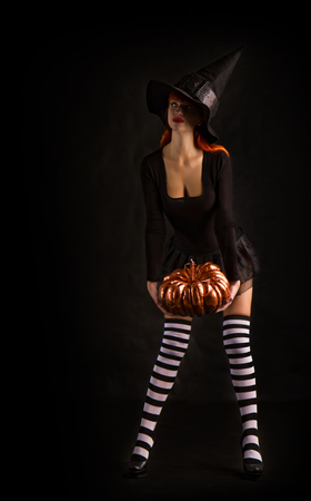 sexy girl dressed as a medieval witch stands with a pumpkin in their hands