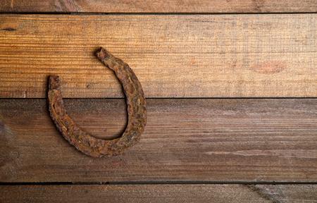 un ferro di cavallo molto vecchio e arrugginito simbolo di fortuna su un semplice sfondo di legno