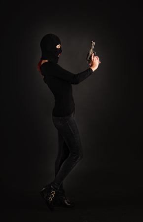 Slim sexy girl in dark inconspicuous clothes hiding her face under a balaclava hat with a gun on a gray background 免版税图像