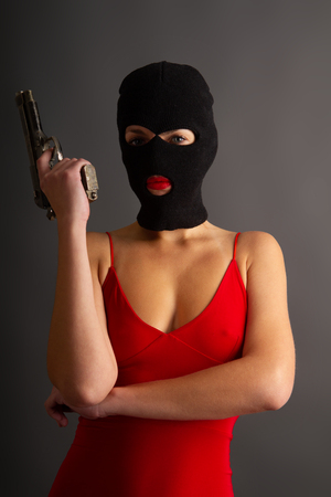 Young self-confident girl with a big gun in a black balaclava and in a red sexy dress standing on a gray background Foto de archivo