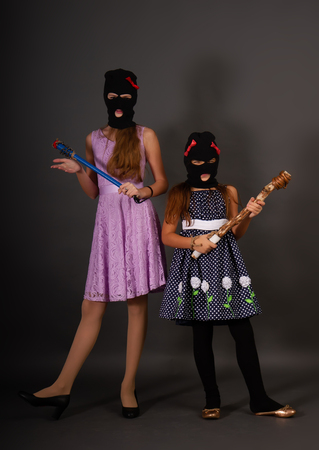 Two teenage hooligans in bright elegant dresses, but in gangster balaclava hats with heavy truncheons pose on a dark background